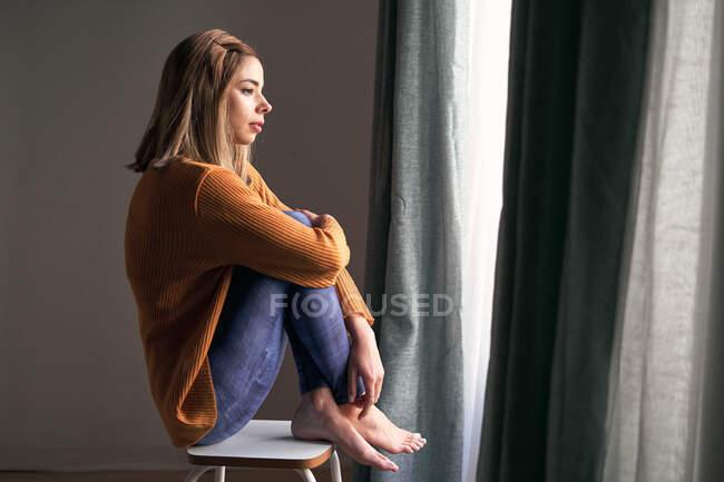 Vue latérale de femme réfléchie en tenue décontractée avec les bras croisés regardant par la fenêtre assis à la maison — Photo de stock
