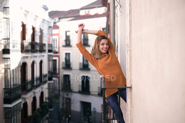 Bright young lady in casual clothes with raised hands standing at balcony looking at camera — Stock Photo