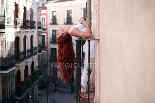 Vue latérale de la jeune femme calme en vêtements de sport avec les yeux fermés avec geste namaste penché en arrière faire du yoga au balcon — Photo de stock