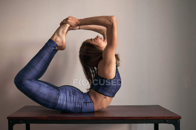 Side view of happy young woman in tracksuit doing yoga Dhanurasana exercise practicing meditation in Bow Pose lying on table at home looking up — Stock Photo