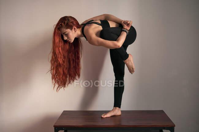 Seitenansicht einer fokussierten Frau mit geschlossenen Augen und Händen hinter dem Rücken, die Yoga im Stehen macht, in geteilter Haltung auf dem heimischen Tisch — Stockfoto