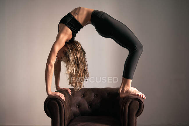 Бічний погляд на мирну жінку в спортивному одязі з закритими очима робить йогу в Колесо По на кріслі вдома — стокове фото