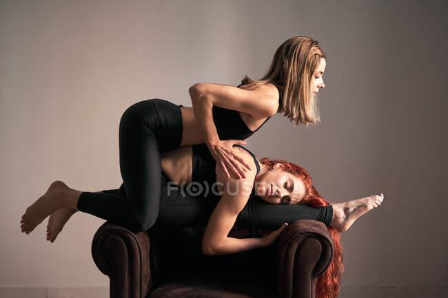 Бічний погляд на щасливу жінку в спортивному одязі з закритими очима робить йогу в Seated Forward Bend Pose на кріслі практикує медитацію з усміхненим другом вдома — стокове фото