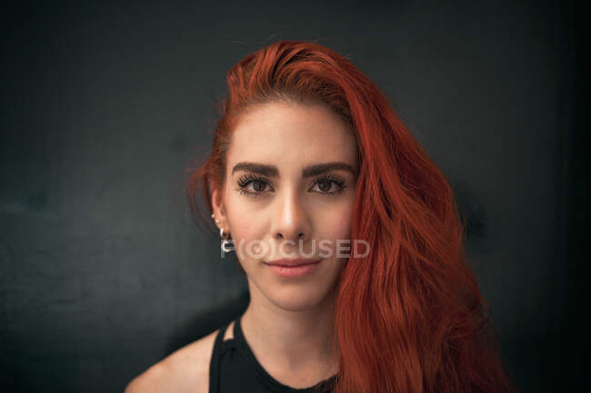 Calm gorgeous young lady with red hair standing at home looking at camera — Stock Photo