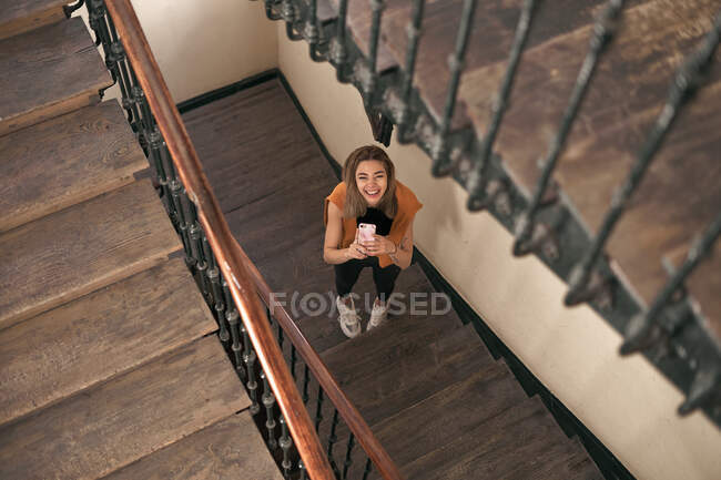 From above of cheerful smiling young woman having fun using phone standing on stairs at home looking at camera — Stock Photo