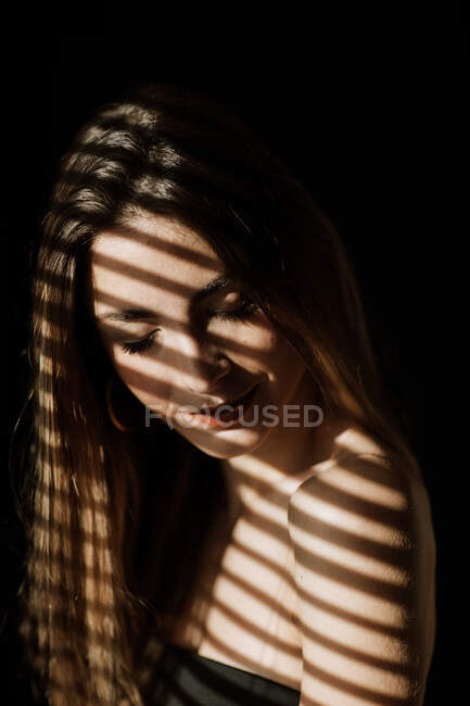 Stripe shadow from shutters falling on face of charming relaxed long haired woman smiling with closed eyes — Stock Photo