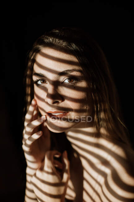 Stripe shadow from shutters falling on face of charming relaxed long haired woman smiling looking at camera — Stock Photo