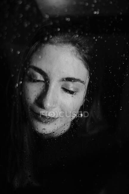 Bianco e nero di donna sorridente in piedi dietro vetro in gocce d'acqua superficie toccante con gli occhi chiusi — Foto stock