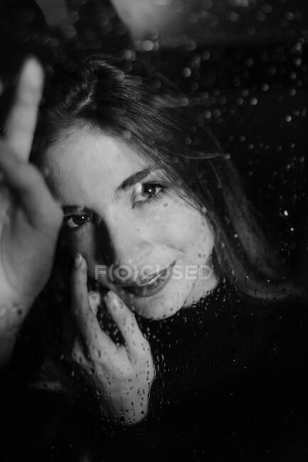 Black and white of smiling woman standing behind glass in water drops touching surface and looking at camera — Stock Photo