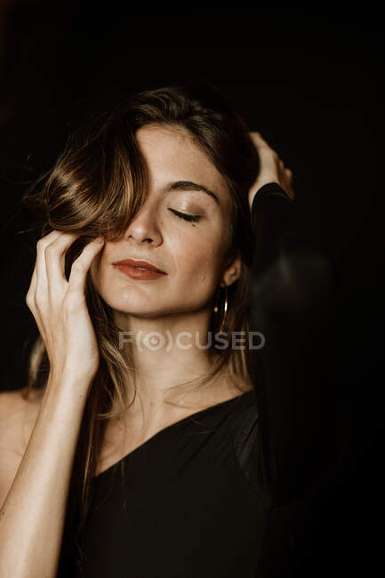 Sensual gorgeous woman in dark dress touching long shiny hair and thinking with closed eyes — Stock Photo