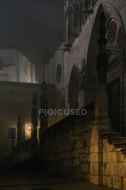 Stone fence with crosses located in dimly illuminated courtyard of aged cathedral at dark night in Burgos, Spain — Stock Photo