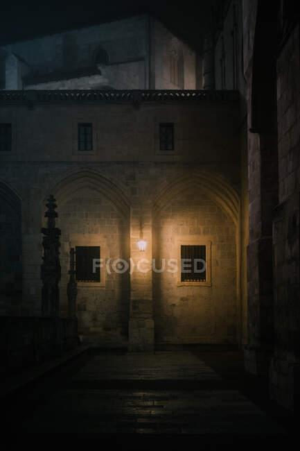 Каменный забор с крестами, расположенный в смутно освещенном внутреннем дворе старого собора в темную ночь в Бургосе, Испания — стоковое фото