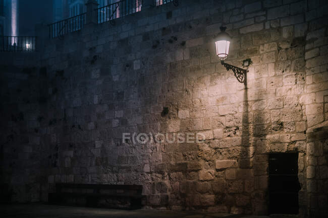 Old fashioned lantern illuminating shabby stone wall of aged cathedral at dark night in Burgos, Spain — Stock Photo