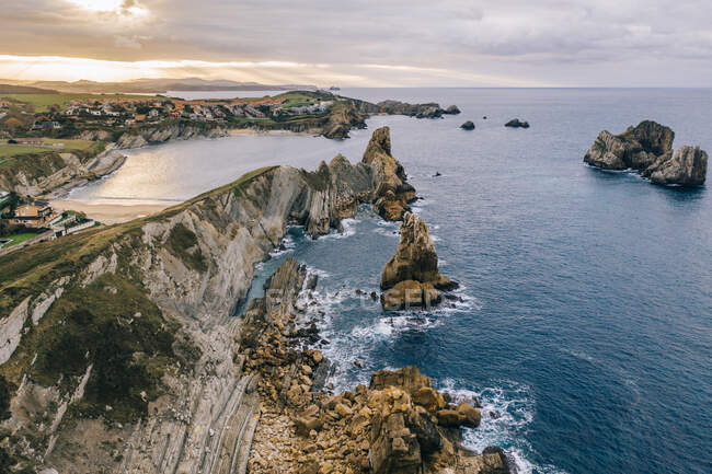 Amazing aerial landscape of steep rocky shore and breathtaking wavy ocean in cloudy day in Pielagos, Cantabria, Santander, Spain — Stock Photo