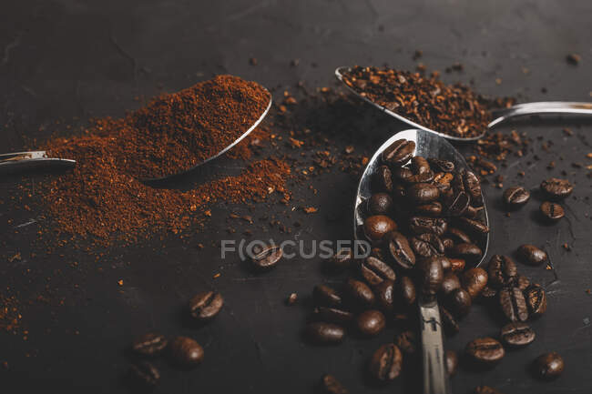 Types of coffee grounds instant and powder and coffee beans in spoons on black table — Stock Photo