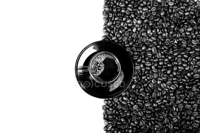 Top view of black cup of coffee on plate with coffee beans isolated on white background — Stock Photo