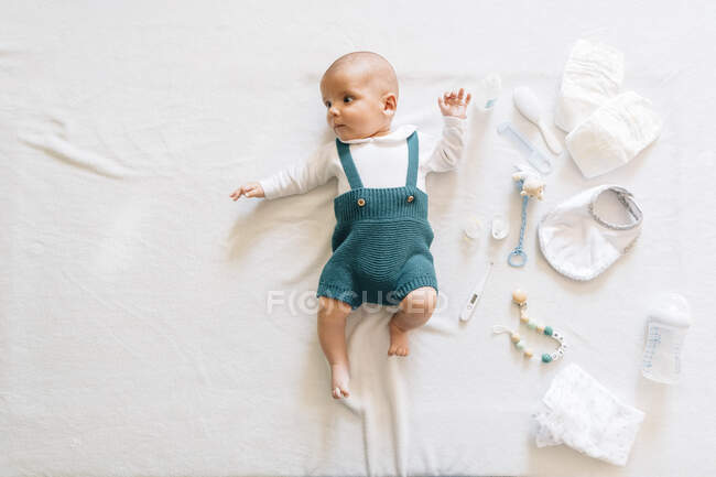 Top view of surprised newborn infant in casual wear lying on bed near toys looking away — Stock Photo