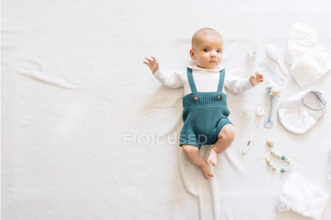 Зверху ви бачите дивного новонародженого в повсякденному одязі, який лежить на ліжку біля іграшок, що дивляться на камеру. — стокове фото