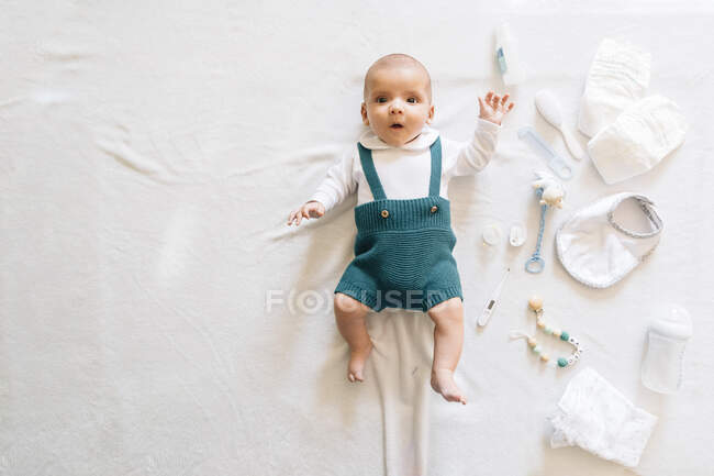 Top view of surprised newborn infant in casual wear lying on bed near toys looking at camera — Stock Photo