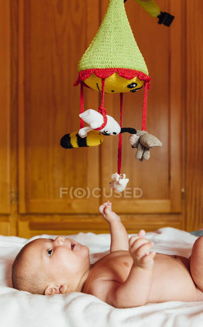 Side view of cheerful naked baby with open mouth playing with toy lying on bed having fun at home — Stock Photo