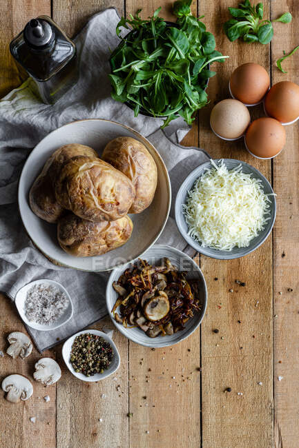 From above bowls with brows stuffed potatoes green herbs fried mushrooms eggs grated cheese and bottle with olive oil on wooden table — Stock Photo