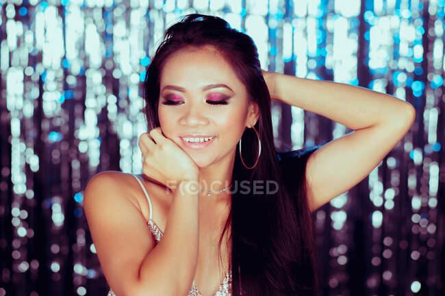 Glamour long chevelu asiatique femme levant la main et regardant vers le bas avec sourire sur fond de mousseux mur — Photo de stock