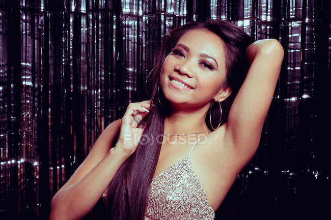 Glamorous long haired asian woman raising hand and looking at camera with smile on background of sparkling wall — Stockfoto
