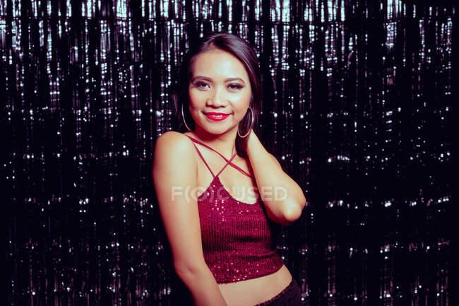 Glamour long chevelu asiatique femme levant la main et regardant caméra avec sourire sur fond de mousseux mur — Photo de stock