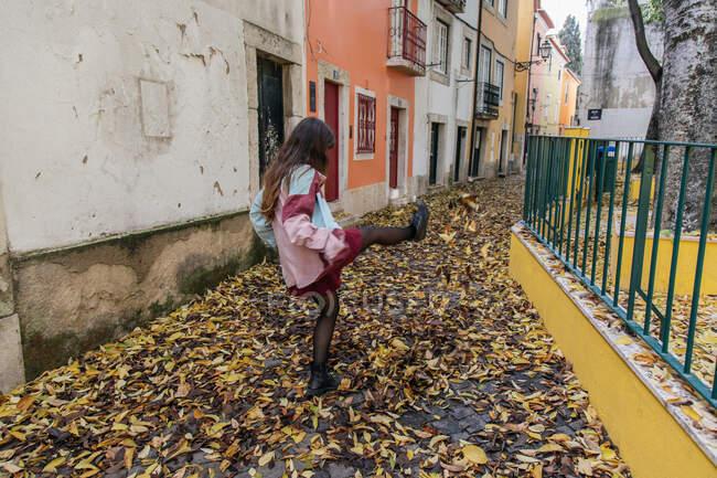 Retour vue anonyme jeune femme active donnant des coups de pied feuilles d'automne lors d'une promenade dans la rue de Lisbonne — Photo de stock
