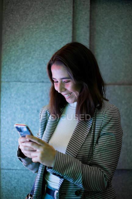 Сконцентрована жінка в стильному повсякденному одязі з бездротовими навушниками і мобільними телефонами на вулицях міста під неоновим світлом. — стокове фото