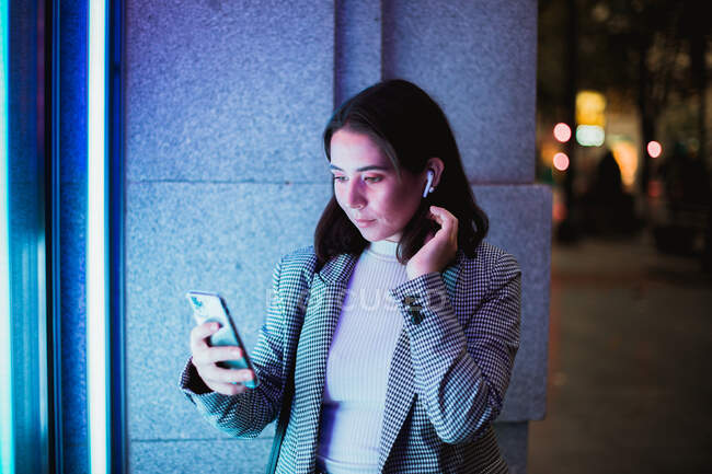 Mujer concentrada en elegante atuendo casual usando auriculares inalámbricos y teléfonos móviles en la calle de la ciudad con luz de neón - foto de stock