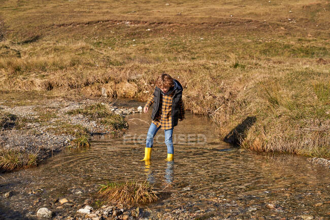 Adorable enfant en bottes en caoutchouc jaune debout dans une petite rivière au pied de montagnes enneigées pierreuses par temps lumineux — Photo de stock
