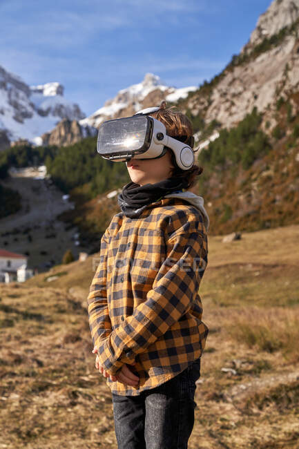 Активный умный мальчик, смотрящий в очки VR, стоящие на камне в горной долине — стоковое фото