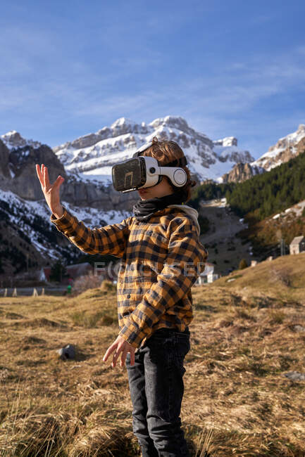 Active smart boy looking away in VR glasses standing on stone in mountain valley — Stock Photo