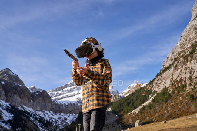 Active smart boy looking away in VR glasses playing with stick standing on stone in mountain valley — Stock Photo