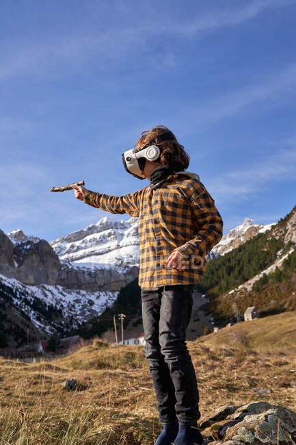 Active smart boy looking away in VR glasses playing standing on stone in mountain valley — Stock Photo