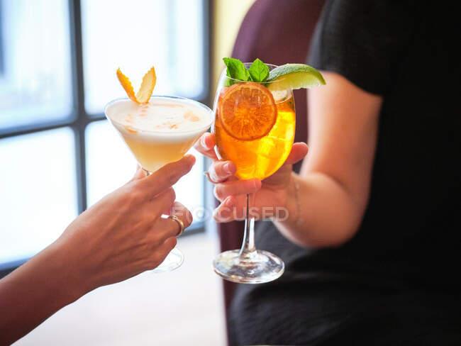 Руки безликих жінок, що чіпляються за стильні окуляри зі свіжими прохолодними алкогольними коктейлями, прикрашеними цитрусами в ресторані. — стокове фото