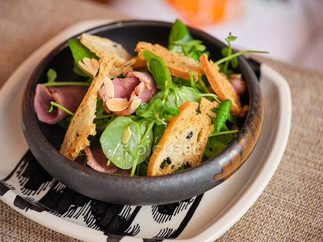 From above of pink roast beef with green salad and crusty bread in black stylish bowl on table in restaurant — Stock Photo