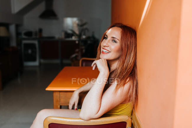 Side view from above of redhead content woman laughing and looking away while resting on chair in modern kitchen — Stock Photo