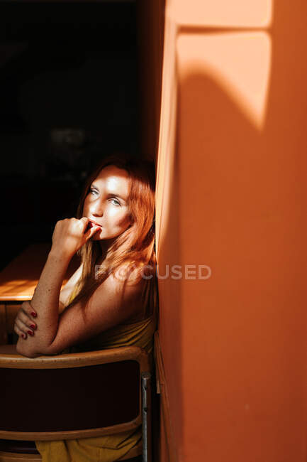 Side view of model in stylish yellow dress with makeup sitting on chair and looking at camera under beam of sun in dark room — Stock Photo