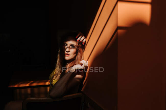 Side view of thoughtful model in stylish yellow dress with makeup sitting on chair and looking away — Stock Photo