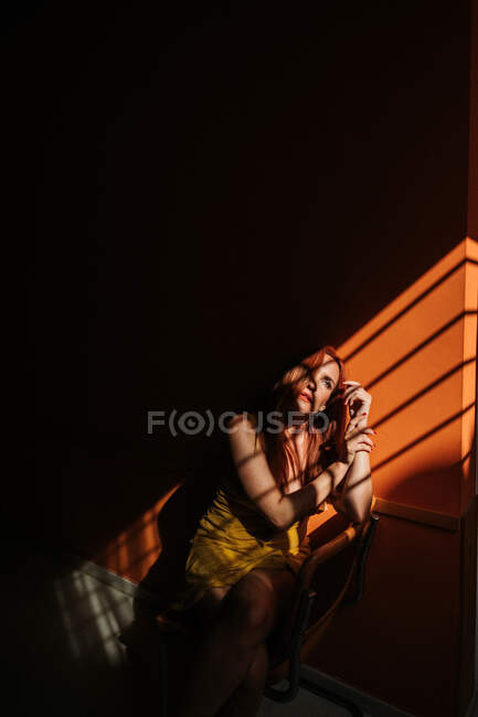 Sensual model in stylish yellow dress with makeup sitting on chair and looking away under beam of sun in dark room — Stock Photo