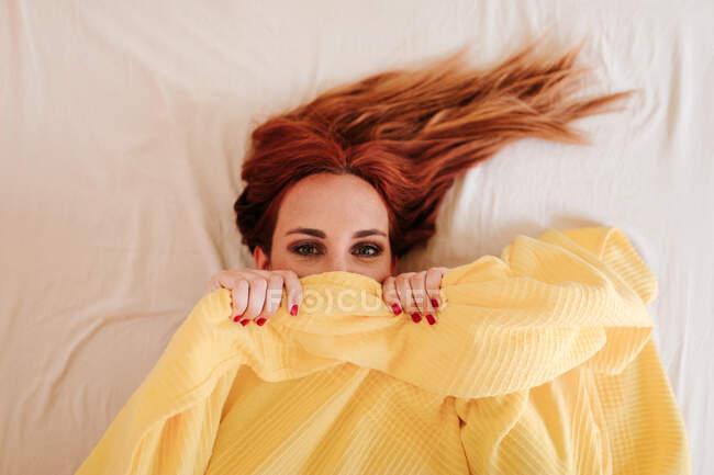 Vue du dessus de surprise rousse drôle de femme souriante tout en regardant sous la couverture jaune à la maison — Photo de stock