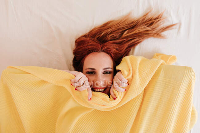 Top view of surprised redhead funny woman smiling while looking out from under yellow blanket at home — Stock Photo