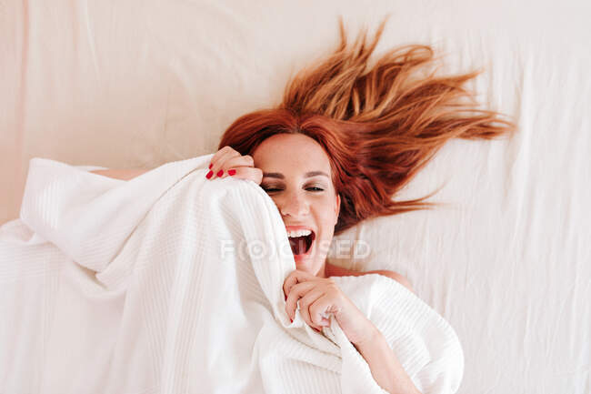 From above top view of surprised redhead funny woman smiling while looking out from under white blanket at home — Stock Photo