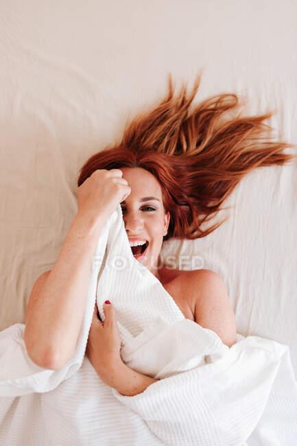 De cima vista superior da mulher engraçada ruiva surpresa sorrindo enquanto olha para fora de baixo cobertor branco em casa — Fotografia de Stock