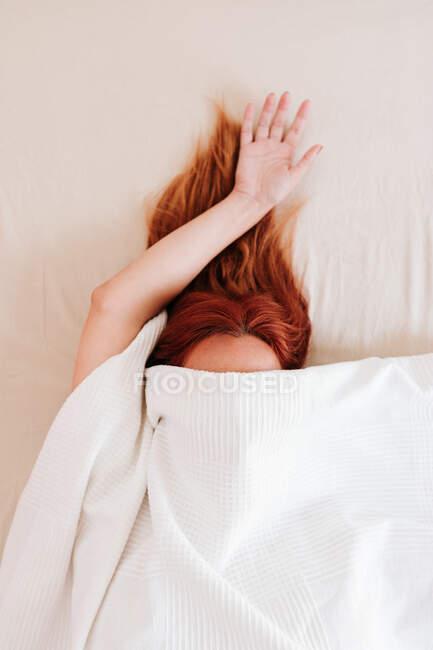Visão superior do cabelo vermelho da senhora sem rosto com braço saliente ter relaxamento enquanto deitado na cama sob lençóis brancos — Fotografia de Stock