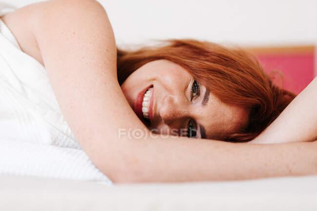 Alegre pelirroja divertida mujer sonriendo mientras mira hacia fuera de debajo de la manta blanca en casa - foto de stock
