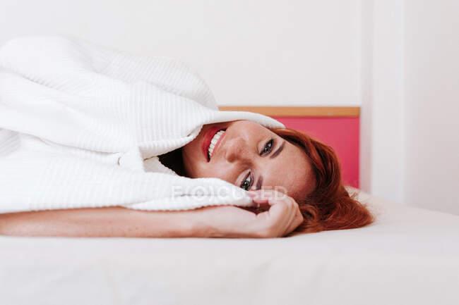 Fröhliche rothaarige lustige Frau lächelt, während sie zu Hause unter einer weißen Decke hervorschaut — Stockfoto