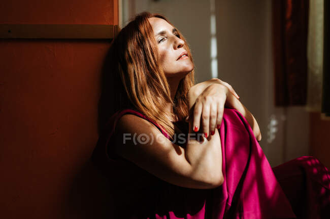 Thoughtful redhead female in stylish pink gown sitting with crossed legs on floor and looking away with rays of sun on face — Stock Photo